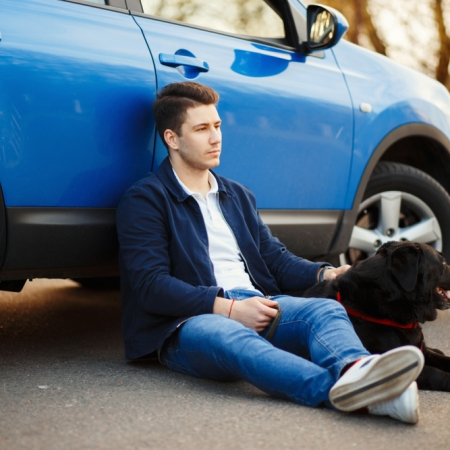 Man and dog sit next to a blue car